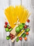 Bestandteile für Spaghettis mit Tomatensauce auf weißem Holztisch Lizenzfreies Stockfoto