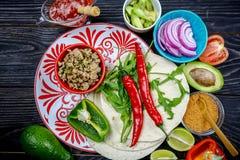 Bestandteile für Tacos: verschiedenes frisches organisches Gemüse und Tortillas auf rustikalem Hintergrund, Draufsicht, mexikanis lizenzfreie stockbilder