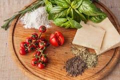 Bestandteile für Teigwaren auf hölzerner Platte Lizenzfreies Stockfoto