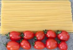 Bestandteile für Teigwaren, Tomate auf grauem Hintergrund Stockfotografie