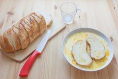Bestandteile für Toast schnitten Weißbrot, die Eier, die mit Milch in der Schüssel mit zwei Scheiben brot auf hölzernem Hintergru Lizenzfreie Stockbilder