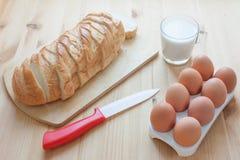 Bestandteile für Toast schnitten Weißbrot, Eier, Milchglas und Messer auf hölzernem Hintergrund Stockfoto