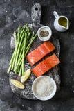 Bestandteile f?r das Mittagessen - frischer roher organischer Lachs, gr?ner Spargel und Reis auf einem dunklen Hintergrund, Drauf stockbild