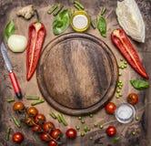 Bestandteile für das Kochen des vegetarischen Lebensmittelgrünen Pfeffers, Messer für Gemüse, Kirschtomaten verzweigen sich und d Lizenzfreie Stockfotos