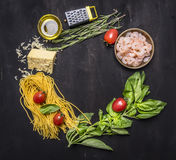 Bestandteile für das Kochen von Teigwaren mit Garnele, Kräuter, Tomaten, Käse zeichneten Rahmenplatz für Draufsicht des hölzernen Stockfoto