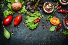 Bestandteile für die geschmackvolle Salatherstellung: Kopfsalatblätter, -champignons, -tomaten, -kräuter und -gewürze auf dunklem Lizenzfreie Stockfotos