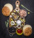 Bestandteile für kuking Hauptburger mit Thunfisch, in Essig eingelegte Gurken, Zwiebeln, Oliven sauce hölzerne rustikale Rückseit Stockfotografie