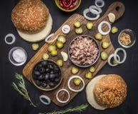 Bestandteile für kuking Hauptburger mit Thunfisch, in Essig eingelegten Gurken, Zwiebeln, Oliven und Soße auf einem Schneidebrett Stockbild