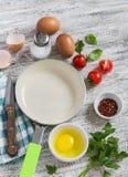 Bestandteile und Geräte für das Kochen von Spiegeleiern mit Tomaten: Eier, Tomaten, Gewürze, Kräuter und Wanne Lizenzfreie Stockbilder
