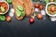 Bestandteile und Verbreitung für das vegetarische Sandwich, das auf dunklem hölzernem Hintergrund macht Stockbilder