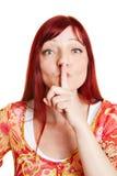 Vrouw die vinger op haar lippen zetten Royalty-vrije Stock Foto's