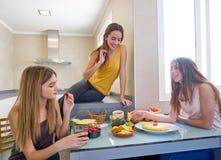 Beste de vriendenlunch die van tienermeisjes bij keuken eten Stock Foto