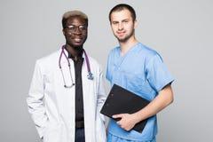 Beste Doktoren Zwei kaukasisch und afroe-amerikanisch lächelnde Doktoren bei der Stellung gegen grauen Hintergrund stockfotografie
