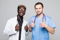 Beste Doktoren Zwei kaukasisch und afroe-amerikanisch lächelnde Doktoren zeigen sich Daumen bei der Stellung gegen grauen Hinterg stockbild