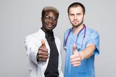 Beste Doktoren Zwei kaukasisch und afroe-amerikanisch lächelnde Doktoren zeigen sich Daumen bei der Stellung gegen grauen Hinterg stockfotos