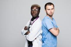 Beste Doktoren Zwei kaukasisch und afroe-amerikanisch Stellung zurück zu hinteren Doktoren gegen grauen Hintergrund lizenzfreies stockfoto