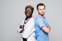 Beste Doktoren Zwei kaukasisch und afroe-amerikanisch Stellung zurück zu hinteren Doktoren gegen grauen Hintergrund lizenzfreie stockfotografie