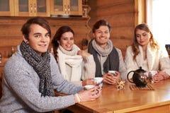 Beste Freunde, die heißen Tee in der angenehmen Küche am Winterhäuschen trinken Lizenzfreies Stockbild