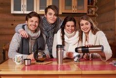 Beste Freunde, die heißen Tee in der angenehmen Küche am Winterhäuschen trinken Stockbild