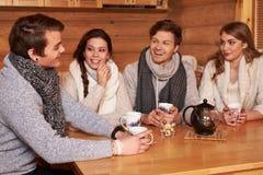 Beste Freunde, die heißen Tee in der angenehmen Küche am Winterhäuschen trinken Lizenzfreie Stockbilder
