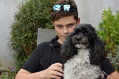 Beste Freunde, Teenager und sein Harlekinpudel lizenzfreie stockbilder