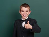 Beste Geste der Schuljungen-Show, Porträt nahe grünem leerem Tafelhintergrund, kleidete im klassischen schwarzen Anzug, ein Schül Lizenzfreies Stockfoto