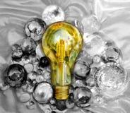 Beste Idee unter anderem, Glühlampe im schönen eviroment mit Schwarzem und mit Kugeln im Hintergrund stockfotos