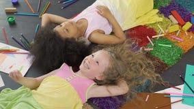 Beste vrienden die bij kleurrijk tapijt en lachen liggen, die van koele vakantie genieten stock videobeelden