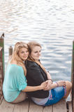 Beste vrienden die op brug door de rivier zitten Stock Foto