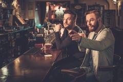 Beste vrienden die pret hebben die op een voetbalspel op TV letten en ontwerpbier drinken bij barteller in bar stock foto's