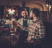 Beste vrienden die pret hebben en ontwerpbier drinken bij bar c stock fotografie