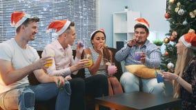 Beste vrienden die toejuichingen maken en partijfluitje op Kerstmispartij blazen stock videobeelden