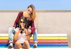 Beste vriendenmeisjes die van tijd samen in openlucht met smartphone genieten Stock Foto