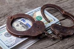 Bestechungsgeld, Geld und Handschellen auf Holztisch Diebstahl des offiziellen Geldes vom Land ` s Budget stockbilder