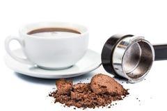 Besteed of gebruikt koffiedik met portafilter en een kop van vers gebrouwen koffie op de achtergrond stock afbeelding