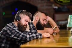 Besteedt de Hipster gebaarde mens vrije tijd bij barteller Ordedranken bij barteller Mensen met hoofdtelefoons en smartphone stock afbeeldingen