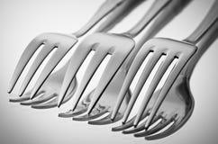 bestek (vorken) op een spiegel in zwart-wit   Stock Afbeeldingen