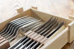 Besteklapje vlees voor persoon zes in houten doos wordt geplaatst die Nieuwe scherpe messen en vorken Het mannelijke concept van  royalty-vrije stock foto