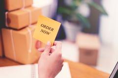 Bestellen Sie jetzt Text auf Post-Itpapier in der Frauenhand an Post w lizenzfreie stockfotografie
