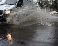 Bestelwagen het drijven door Overstroomde weg bespattende stoep/bestratingen stock foto