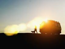 Bestelwagen met een vrouw die haar honden lopen bij zonsondergang Stock Fotografie
