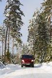 Bestelwagen, 4x4, die op een sneeuwlandweg drijven Stock Fotografie