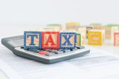 Besteuerungskonzept mit hölzernen Würfeln und Taschenrechner Lizenzfreies Stockbild