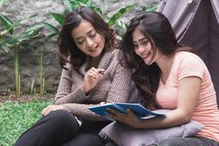 Bestfriend daily activity. Charming girls reading a book near a tent Royalty Free Stock Photography