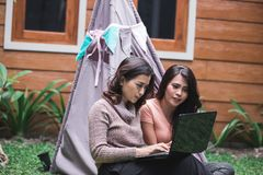 Bestfriend daily activity using laptop. Two young women enjoy playing laptop by sitting near the tent in the backyard Stock Image