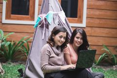 Bestfriend daily activity using laptop. Two young women enjoy playing laptop by sitting near the tent in the backyard Stock Photo