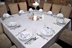 Bestick med färgrika blommor, smycken och vädrade stearinljus förläggas på runda tabeller för de traditionella bröllopen för gäst Arkivbild