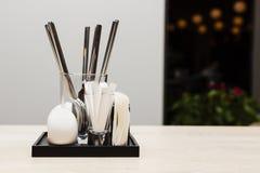Bestick med servetten och tandpetare i aftonkafé Arkivfoto