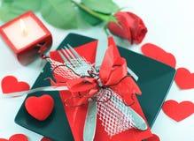 Bestick på den mörka plattan med en stearinljus dekorerade för dag för valentin` s Arkivbild