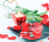Bestick på den mörka plattan med en stearinljus dekorerade för dag för valentin` s Arkivfoton